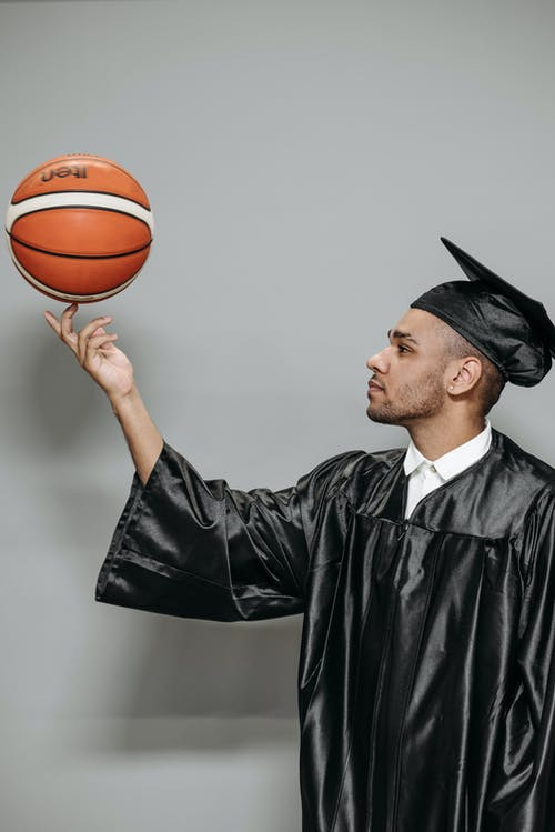 Photo of Man in Black Academic Gown Holding Basketball