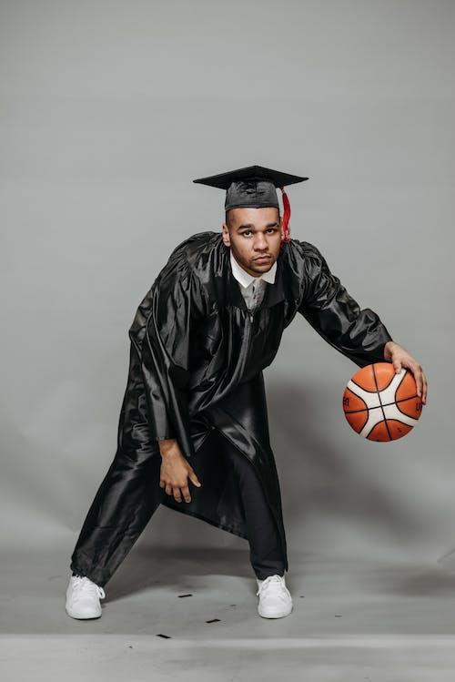 Photo of Man in Black Academic Dress Playing Basketball