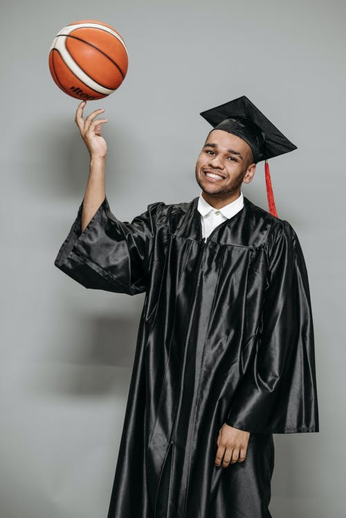 Photo of Man Balancing Basketball on Tip of his Hands