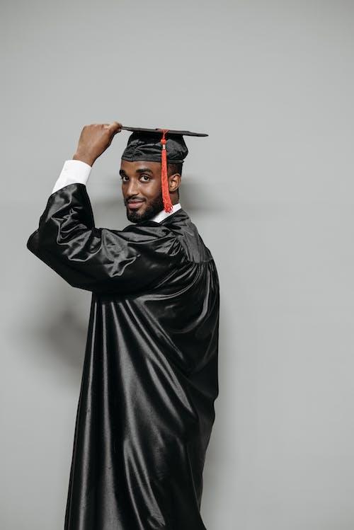 Studio Shot of Man Holding his Graduation Cap