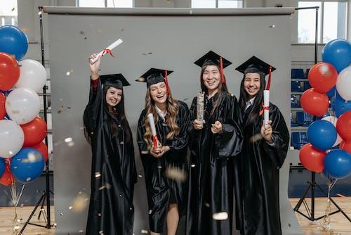 Photo of Happy Women in Black Academic Dress