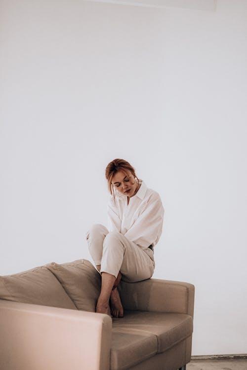 Tender woman sitting on arm of sofa