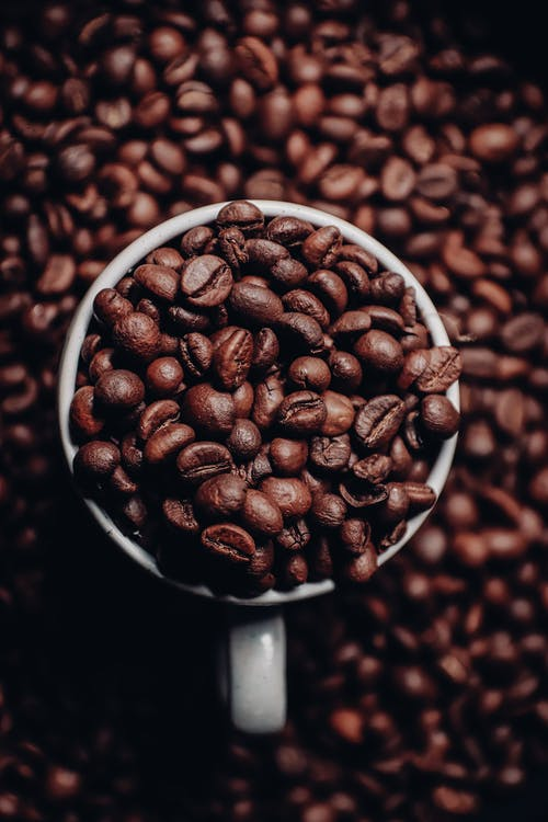Cup of aromatic coffee beans on heap