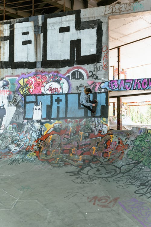 Man Doing Skateboarding Trick On A Wall With Graffiti