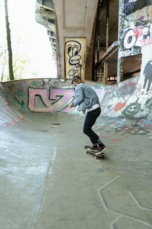 Man in Blue Denim Jacket and Black Pants Riding Skateboard