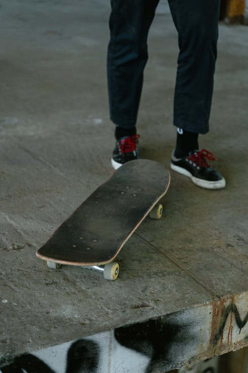 Crop Photo Of Person in Black Pants and Black Sneakers With Skateboard Standing on Gray Concrete Floor