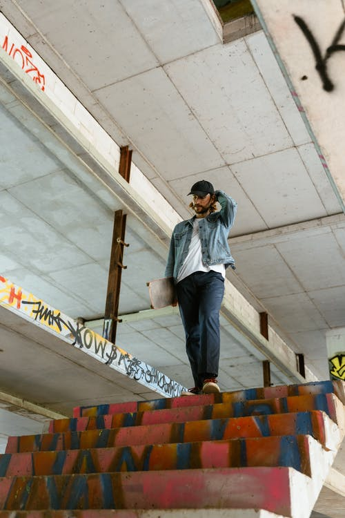 Man in Blue Denim Jacket Standing On Stairs Holding A Skateboard