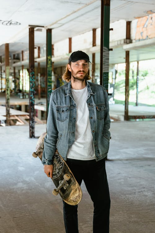 Man in White Crew Neck T-Shirt With Denim Jacket Holding A Skateboard