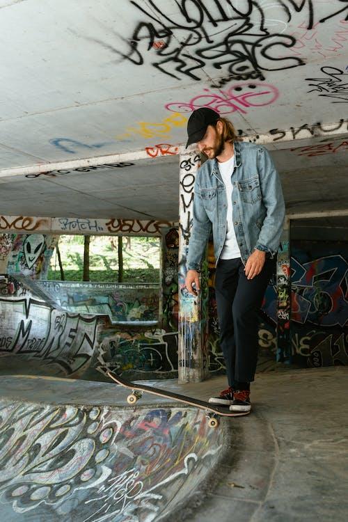 Man in Blue Denim Jacket Standing on a Skateboard