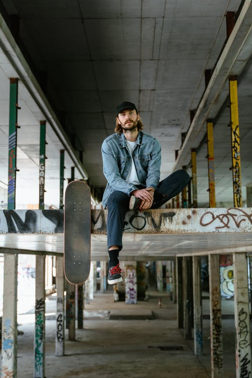 Man in Blue Denim Jacket and Black Pants Sitting on a Beam With Skateboard