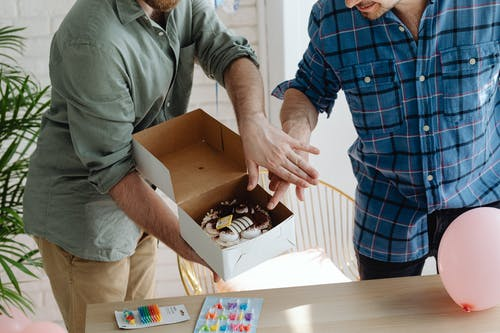 Man in Gray Polo Shirt Holding Brown Box