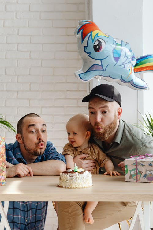 Two Men With A Baby Blowing A Candle On A Birthday Cake