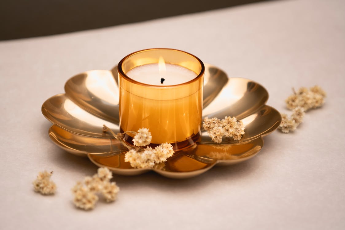 White Pillar Candle on Brown and White Ceramic Saucer