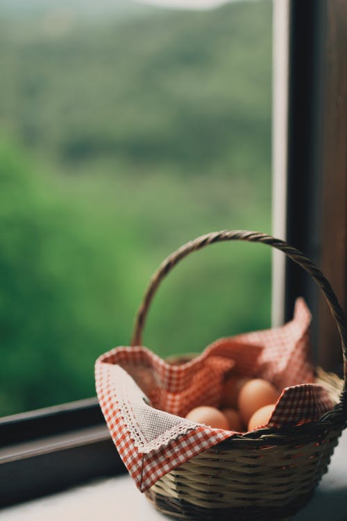 Wicker basket with fresh chicken eggs placed on windowsill in room in daytime