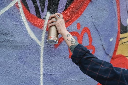 Close-Up Photo of a Person's Hand Spraying White Paint on a Wall