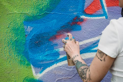 Close-Up Photo of a Person Holding a Blue Spray Paint Can