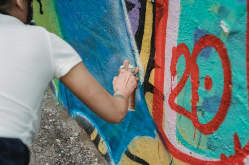Photo of a Person Spraying Paint on a Wall