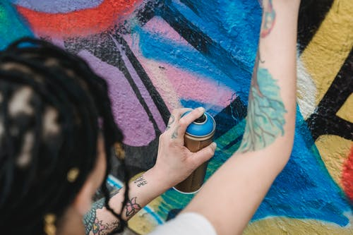 Selective Focus Photo of a Person Spraying Blue Paint on a Wall