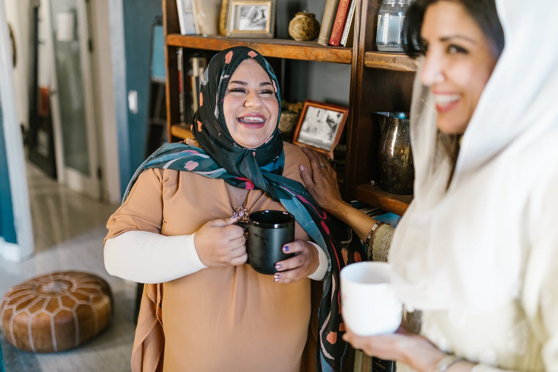 Woman in Brown Hijab Holding Black Ceramic Mug