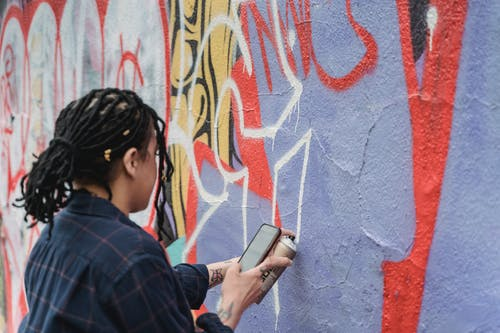 Person Holding a Cellphone While Spraying Paint on a Wall