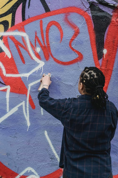 Back View of a Person Spraying White Paint on a Wall