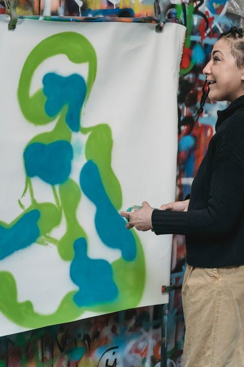 A Woman Doing Graffiti on a Wall Using a Spray Paint