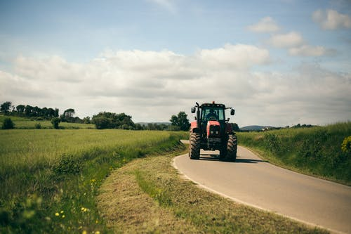 Red Tractor on Brown Dirt Road