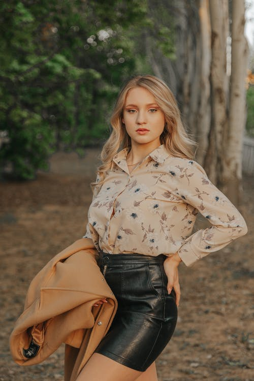 Trendy model with hand on hip in park