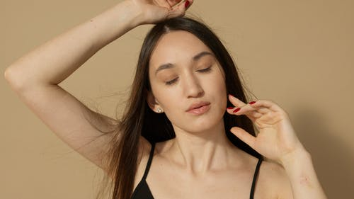 Close-Up Photo of a Woman with Red Fingernails Posing with Her Eyes Closed