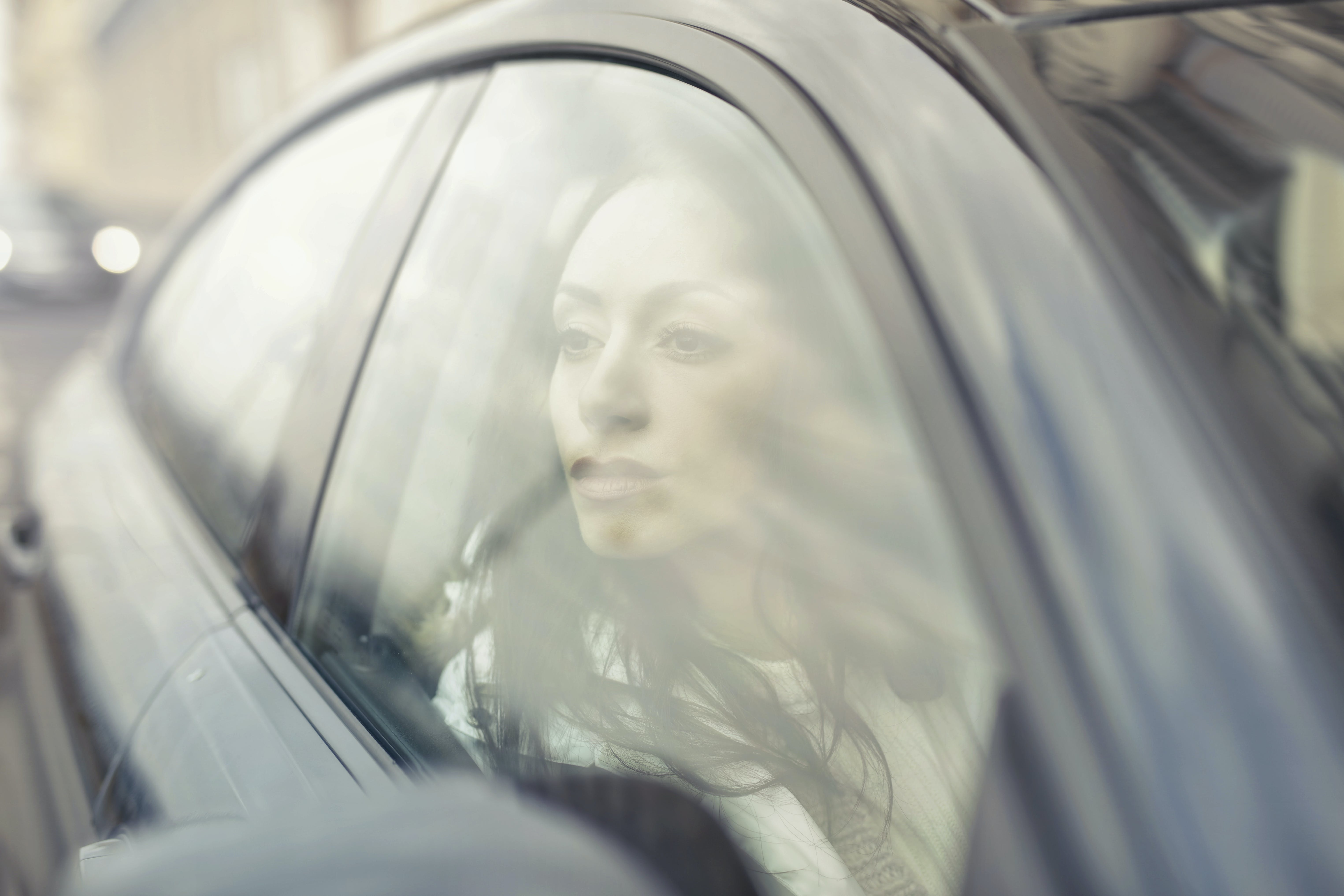Woman Inside the Black Sedan at Daytime