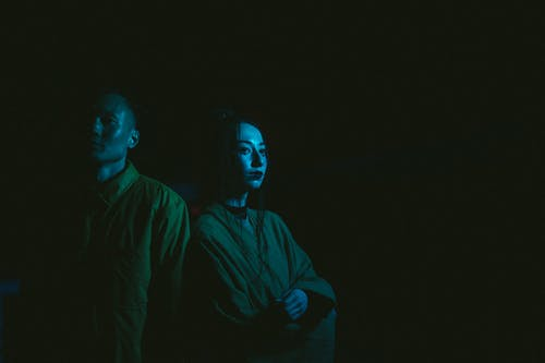 Photo Of Man And Woman With Blue Light Reflection On Black Background