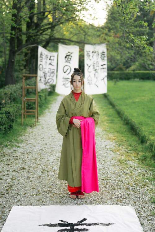 Woman in Green Kimono Standing On Pathway
