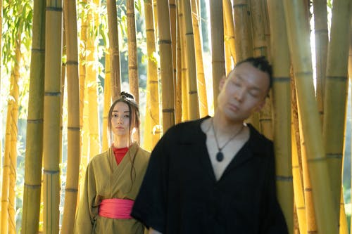 Man And Woman In Their Traditional Wear Standing Near Bamboo Stalks