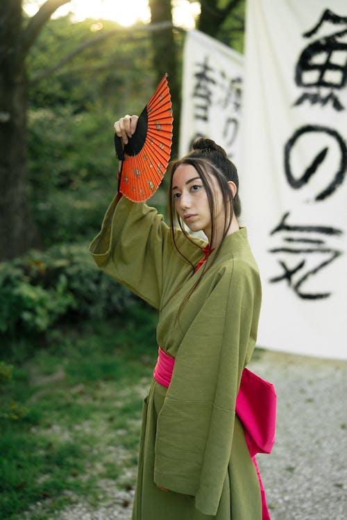 Woman in Green Kimono Holding A Hand Fan