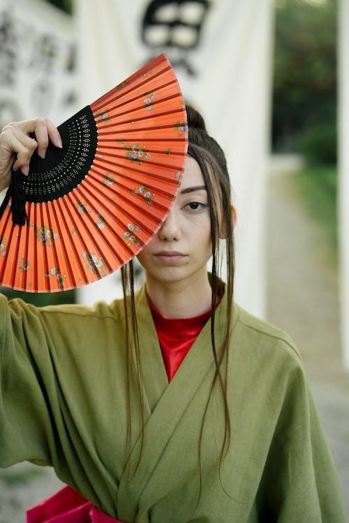 Woman in Green Blazer Holding Hand Fan