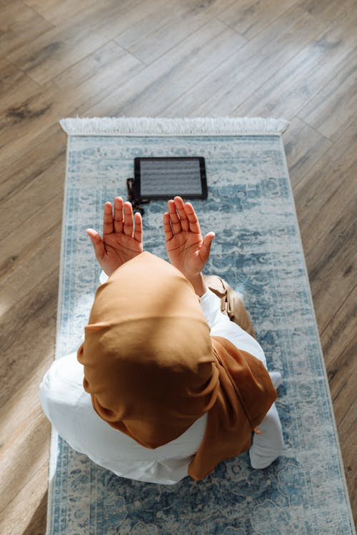 High-Angle Shot of a Person Kneeling on a Blue Prayer Rug