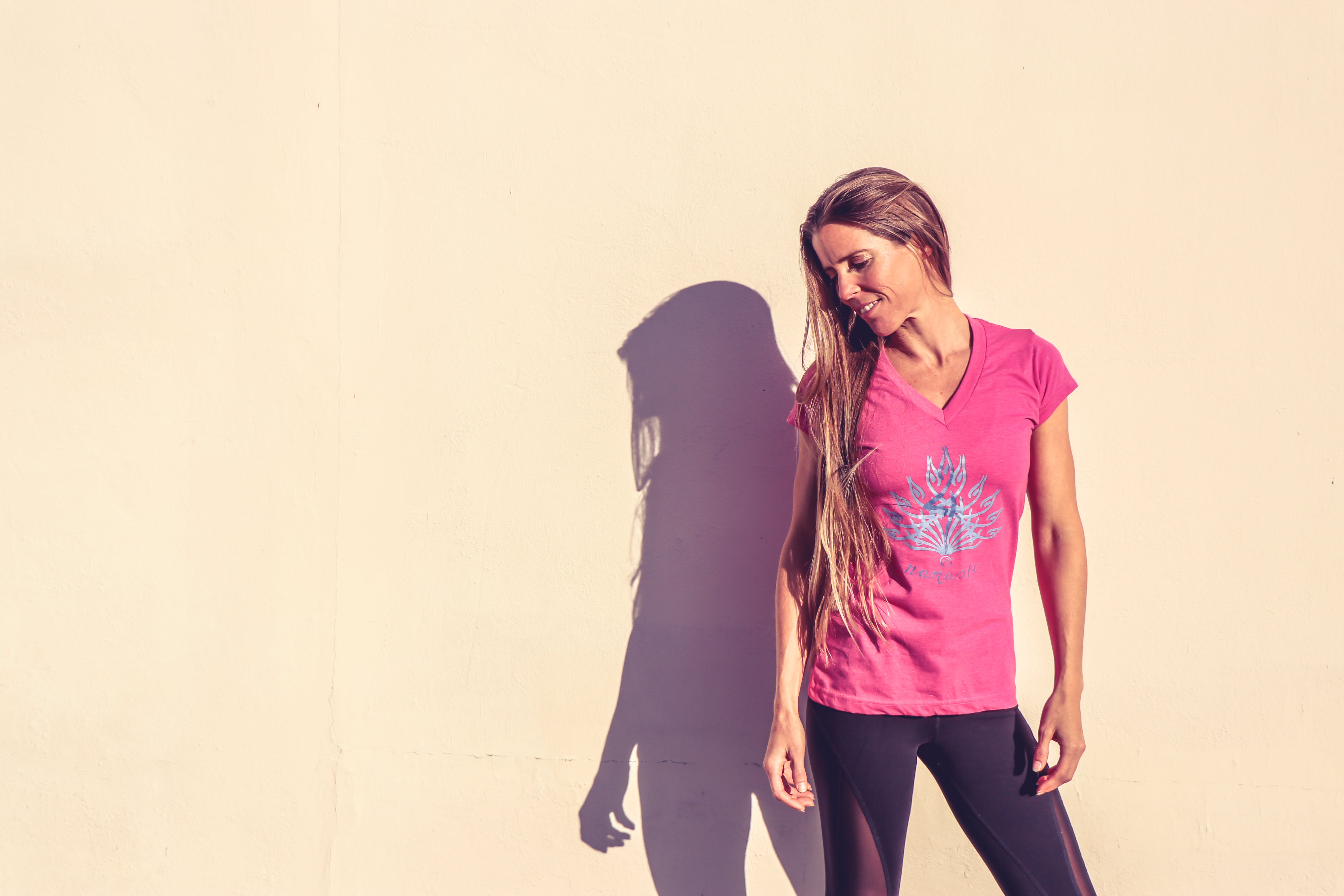 Woman in Pink V-neck Cap-sleeved Shirt Standing Near Wall