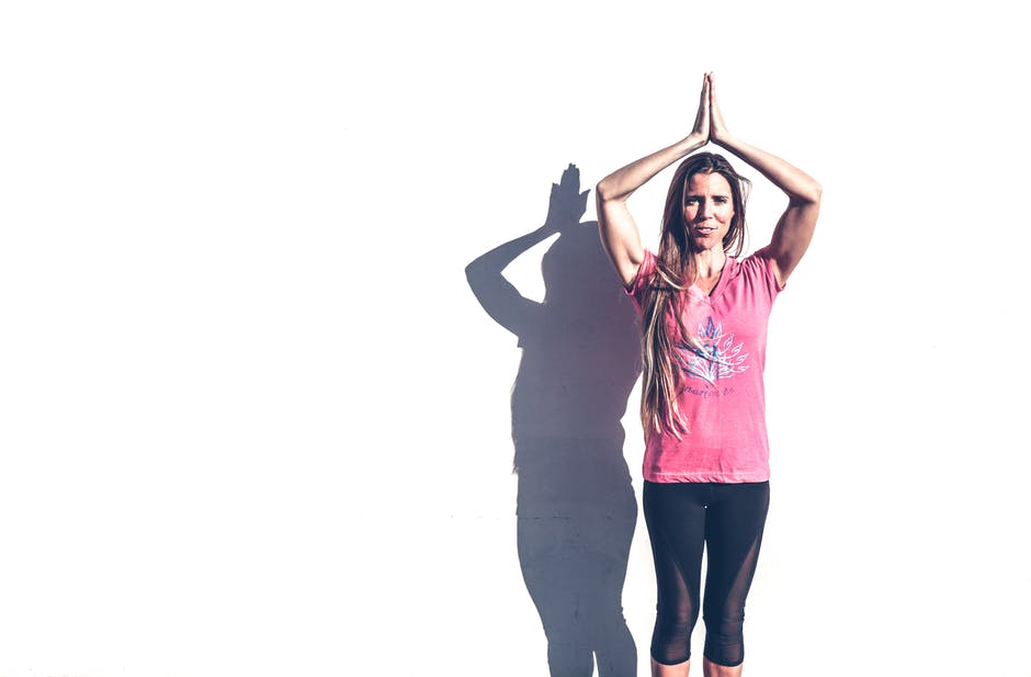 Woman in pink crew neck t shirt and black leggings standing near white wall