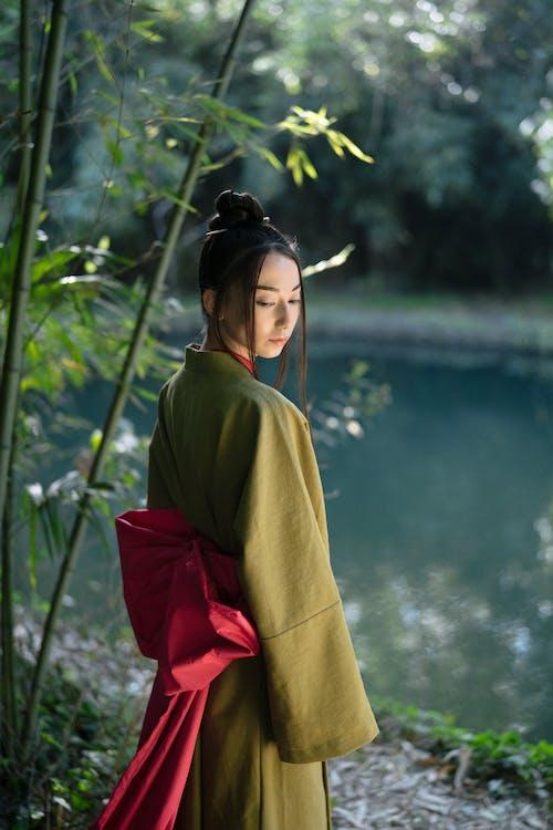 Woman in Green Kimono Standing Near Body of Water