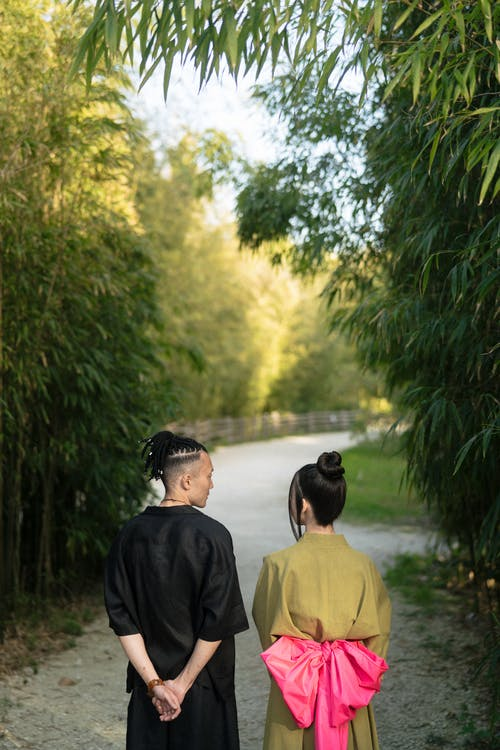 Man and Woman Standing Near Bamboo Trees