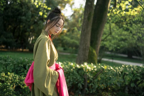 Woman in Green Kimono Standing Near Green Trees