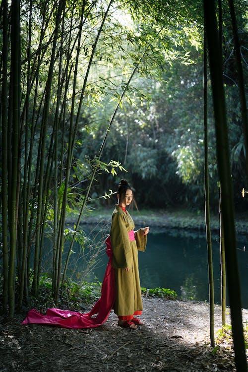 Woman in Green Kimono Standing Near Green Bamboo Trees
