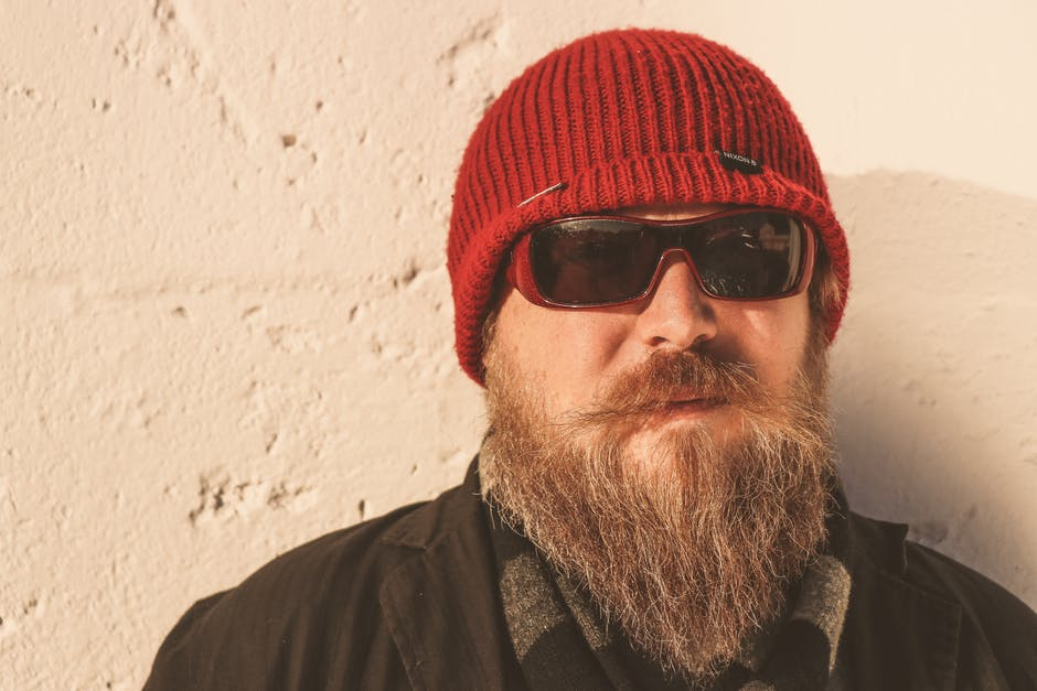 Bearded man wearing red beanie cap sunglasses and black jacket