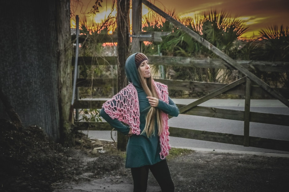Woman in Green Long-sleeved Dress Standing Near Brown Wooden Fence