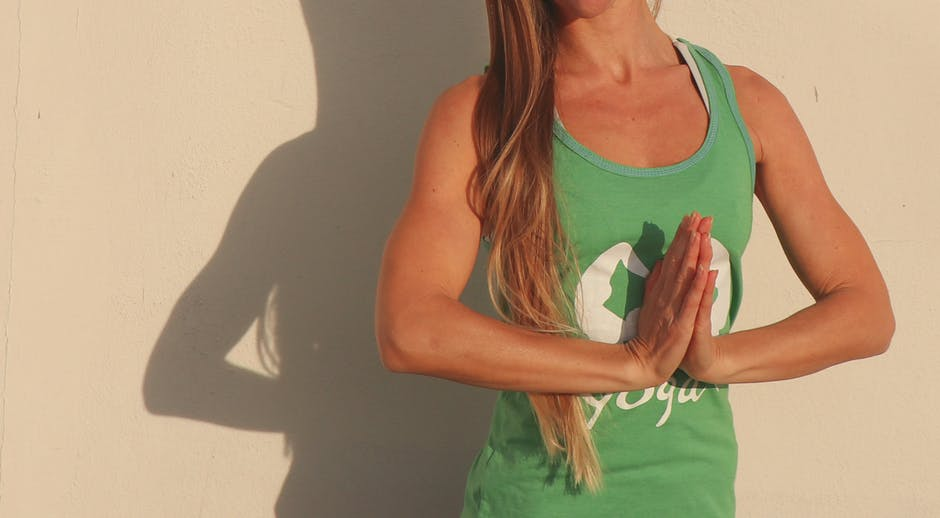 Woman wearing green shirt standing beside wall