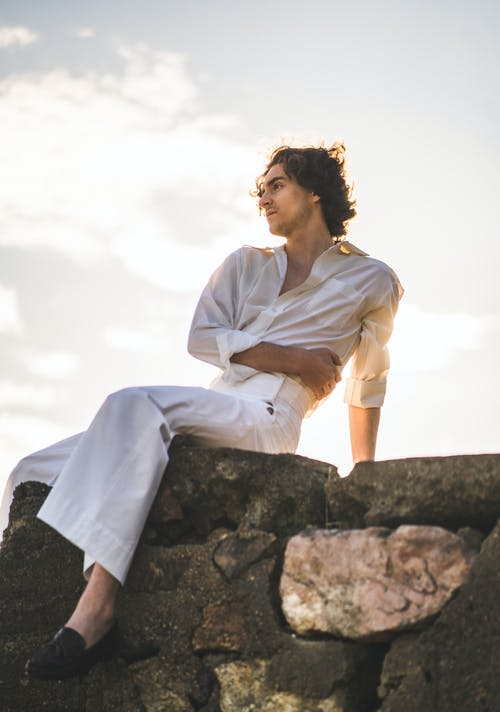 Woman in White Dress Shirt and White Pants Sitting on Rock