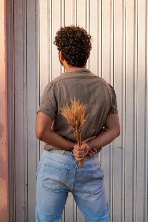 Man in Gray T-shirt and Blue Denim Jeans Holding Broom