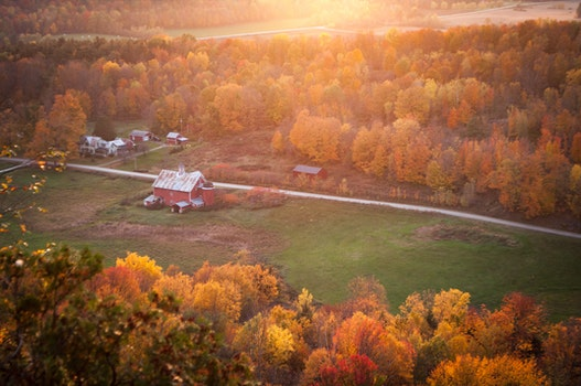 Aerial View of Red and White Painted Barn Near Green Grass Yard