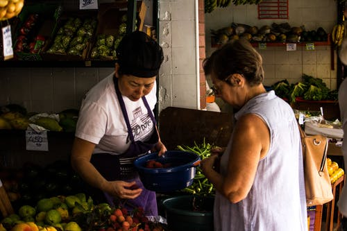Photo of Woman Holding Blue Bucket and Fruit Facing Woman Wearing Blue Sleeveless Shirt