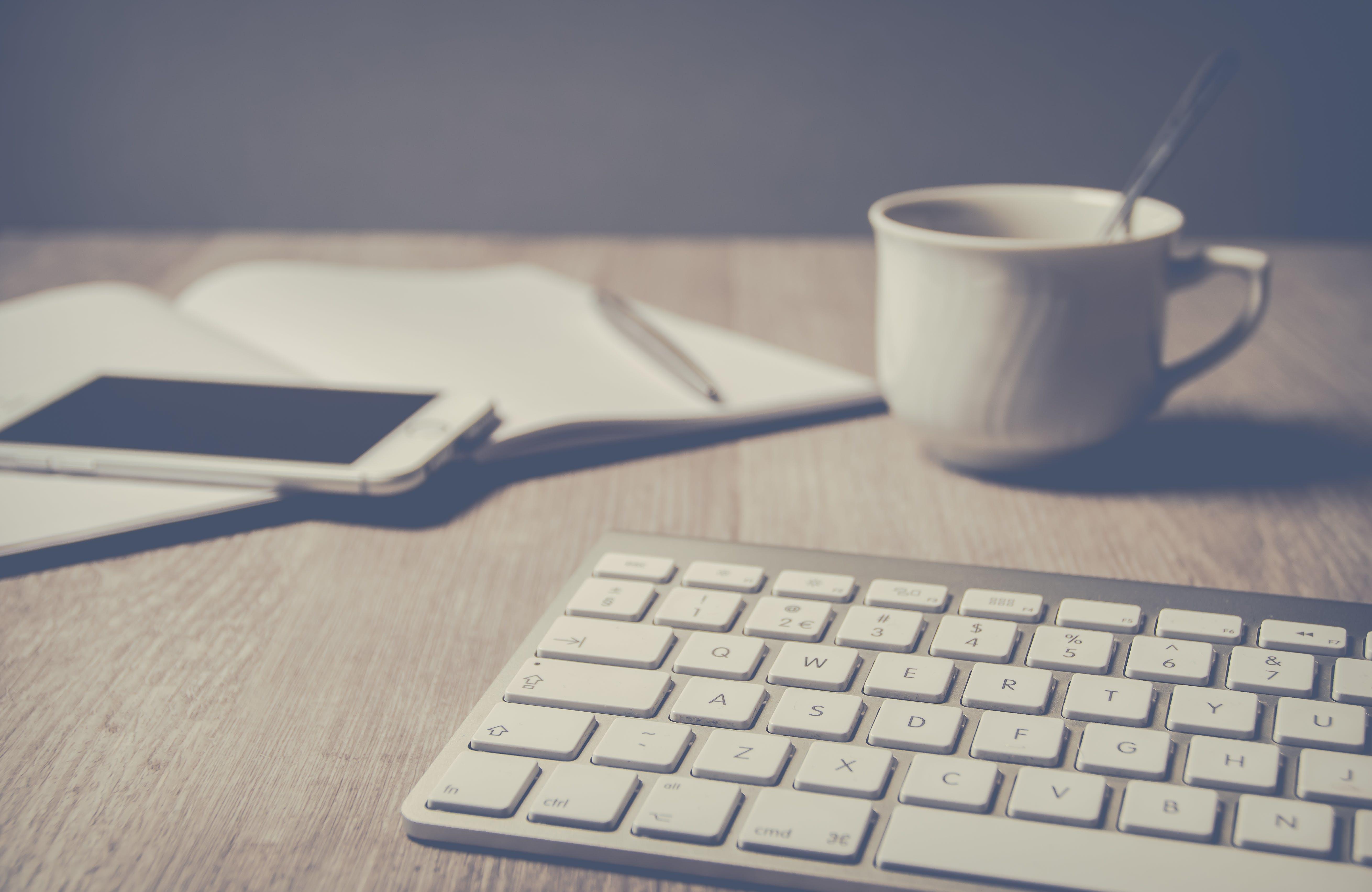 Magic Keyboard Beside Coffee Mug on Desk
